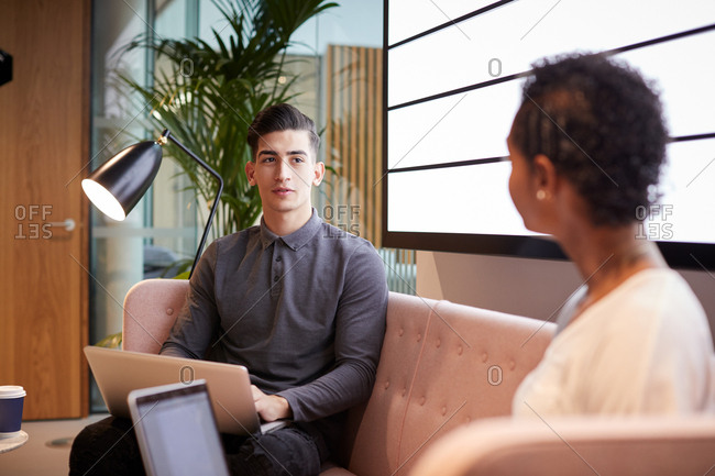 Two young business colleagues sitting on a sofa using laptops and talking at an informal meeting in a casual office, close up