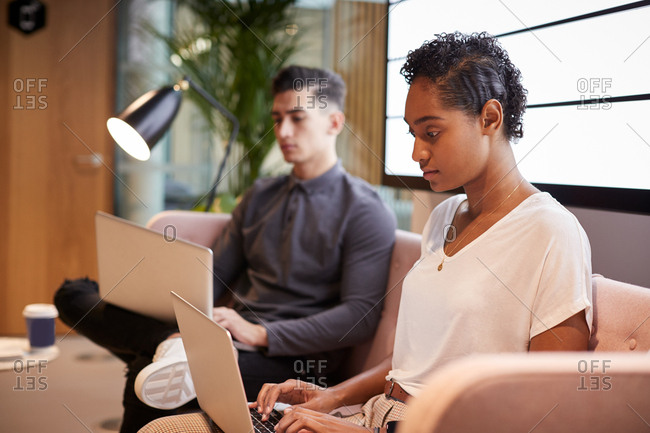 Young male and female business colleagues working on their laptops sitting on a sofa in a casual office, close up