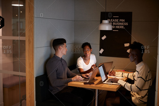 Three young adult technology creatives working together in discussion at a table in a booth at the business canteen