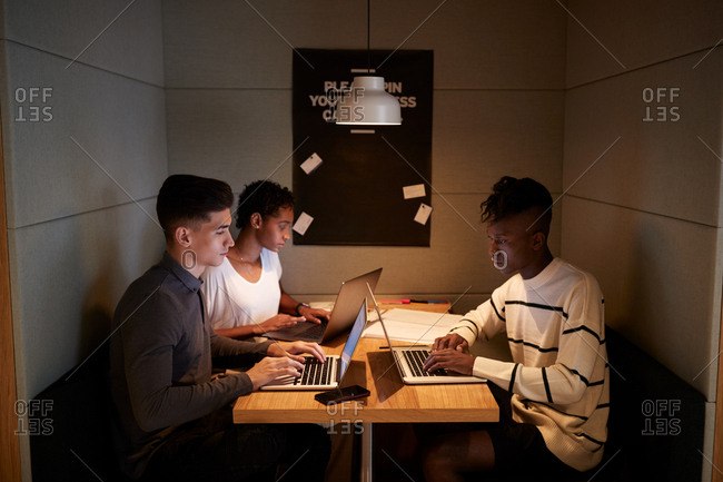 Three young adult technology creatives working together on laptops sitting at a table in a booth at the business canteen, close up