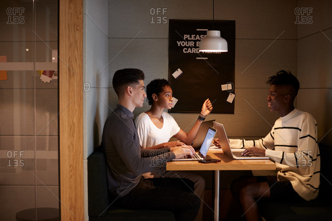 Three young adult technology creatives in discussion, working together sitting at a table in a booth at the business canteen