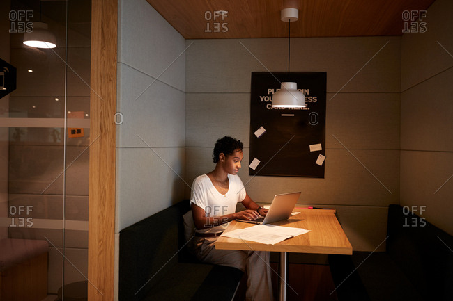 Young woman working alone on a laptop at a table in a casual office space, side view