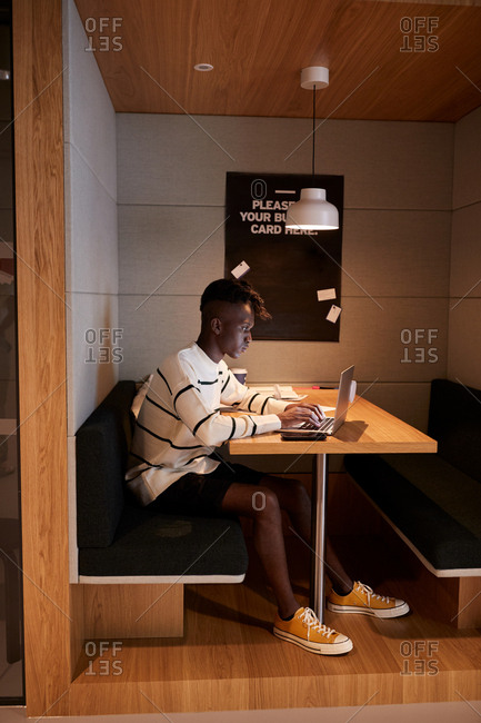 Young man working on a laptop computer at a table in a booth at a workplace canteen, full length, side view