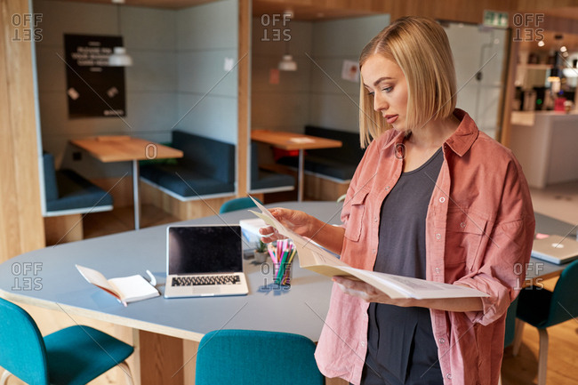 Young female creative standing in her office reading a document, side view, close up