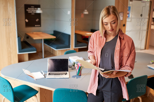 Young female creative standing in her office reading a document, front view, close up