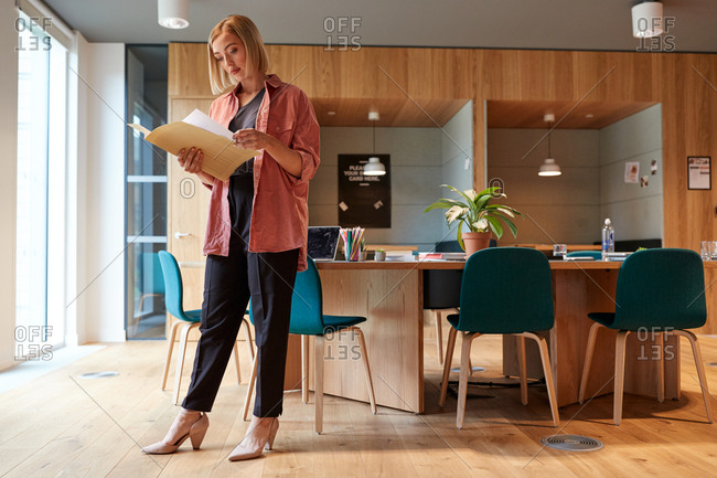 Young creative businesswoman standing in her office reading a document, full length, low angle