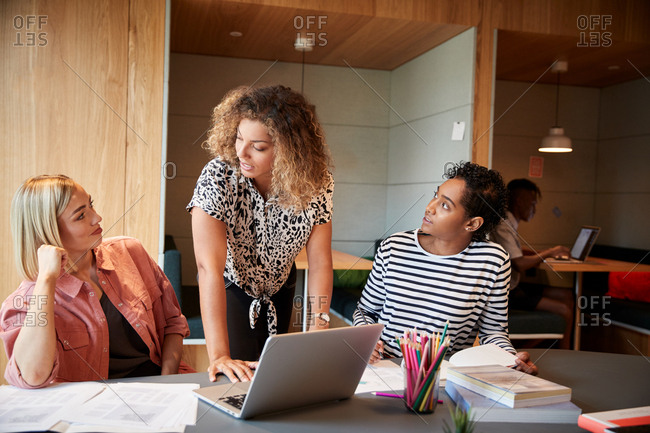 Two young creative businesswomen talking about a project sitting at desk in an office, close up