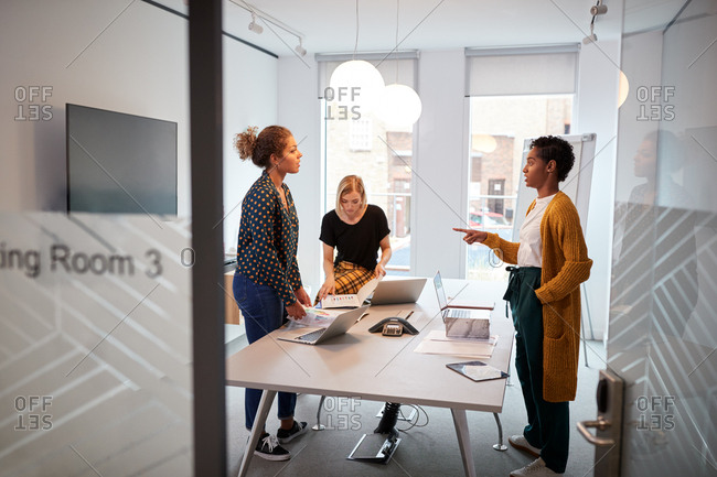 Young creative business team standing around a table at a brainstorm meeting in an office, seen from doorway