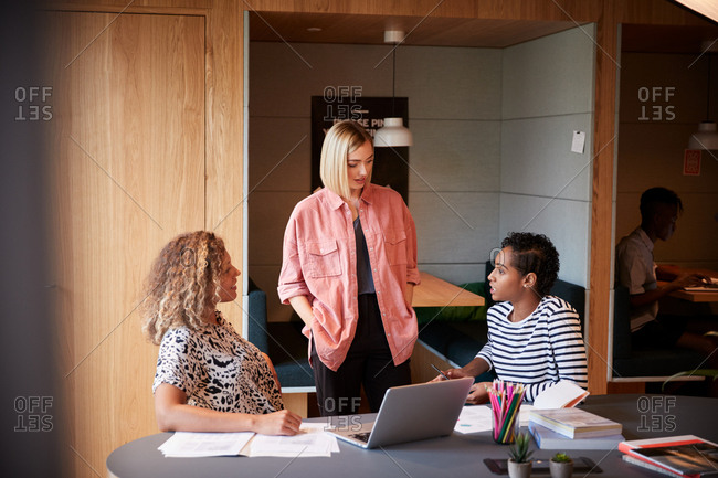 Three smiling young female creatives in discussion in an office meeting room, close up
