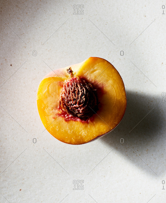 One half of a peach on a kitchen counter