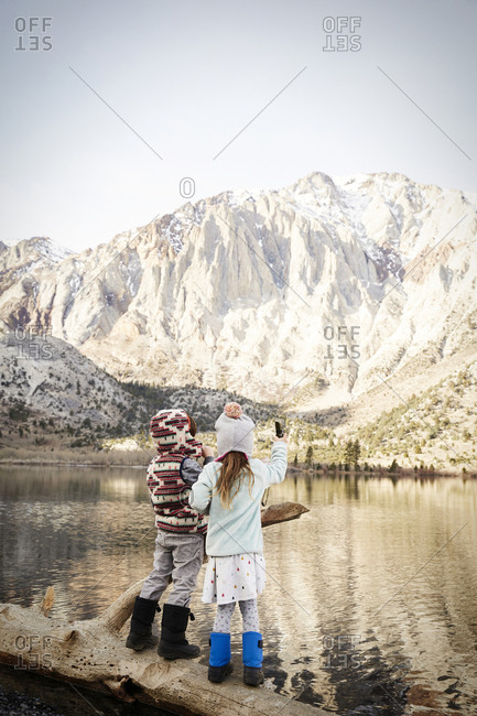 Children standing on a log along the shore of Convict Lake in the Sierra Nevada mountains