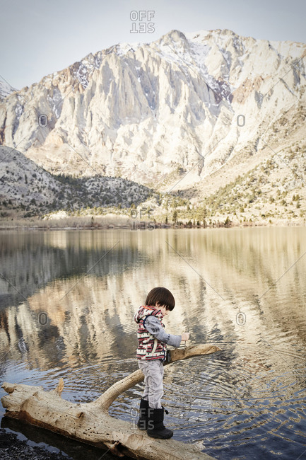 Boy standing on a log along the shore of Convict Lake in the Sierra Nevada mountains