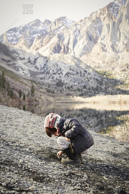 Child looking for rocks along the shore of Convict Lake in the Sierra Nevada mountains
