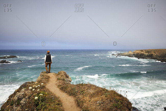 Back view of man standing at scenic overlook along the Northern California coast