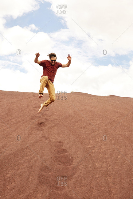 Portrait of millennial jumping off sand dunes