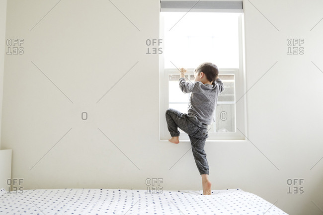 Little boy climbing inside bedroom