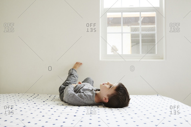 Little boy lying on back in bed looking up