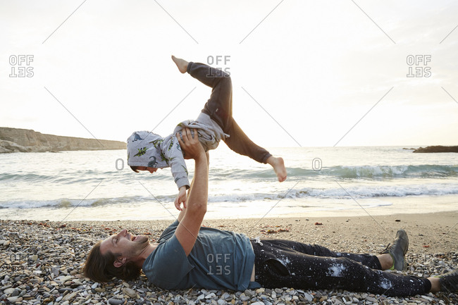 Father holding up child while lying down on the beach