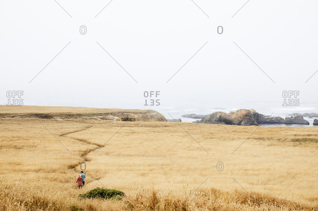 Little River, Mendocino County, California, USA - July 30, 2017: People hiking through a field of tall dry grass along the Van Damme Headlands on the Northern California coast