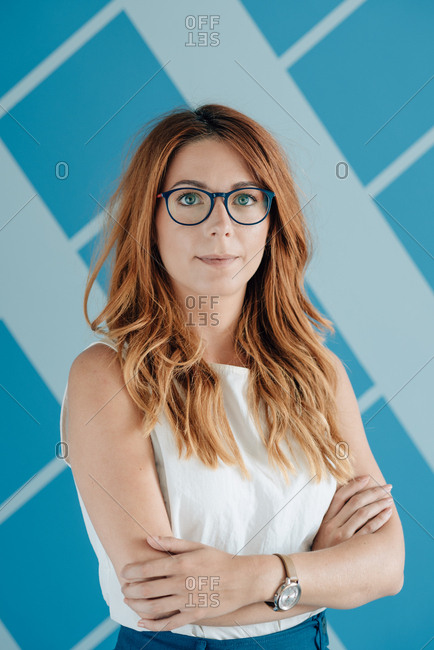 Portrait of young business woman with red hair and glasses