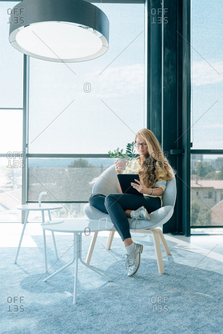 Young blonde woman in office open space drinking tea and holding her tablet