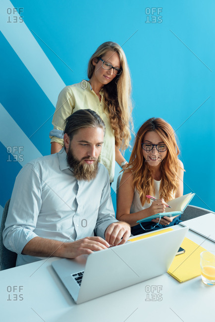 Three young colleagues working together in office