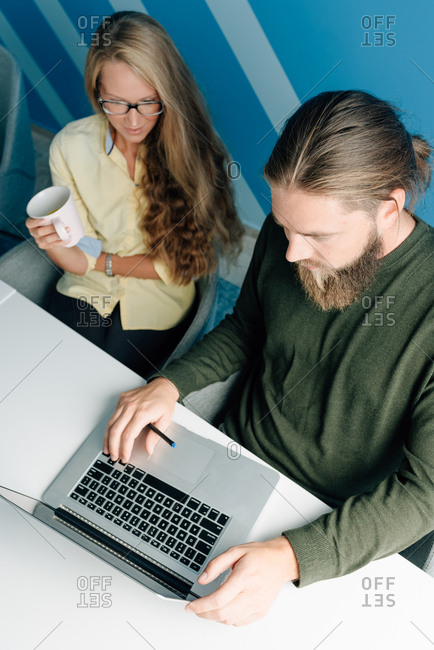 Two young colleagues working together on a laptop in an office