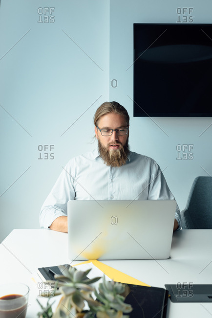 Young man with beard and glasses working on his laptop in his office