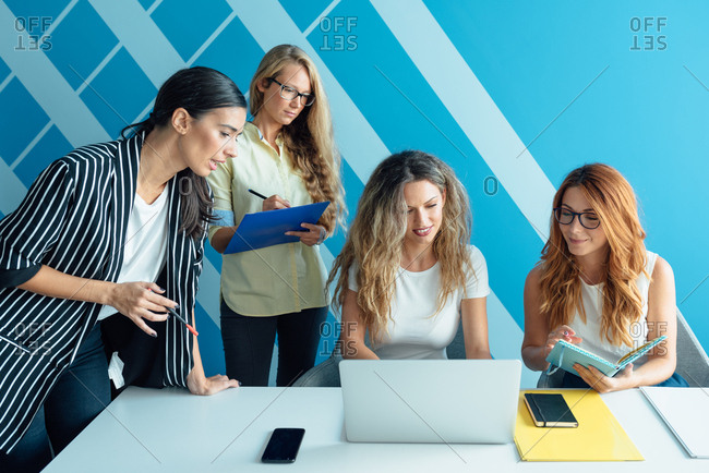Four business women working together on a laptop in an office