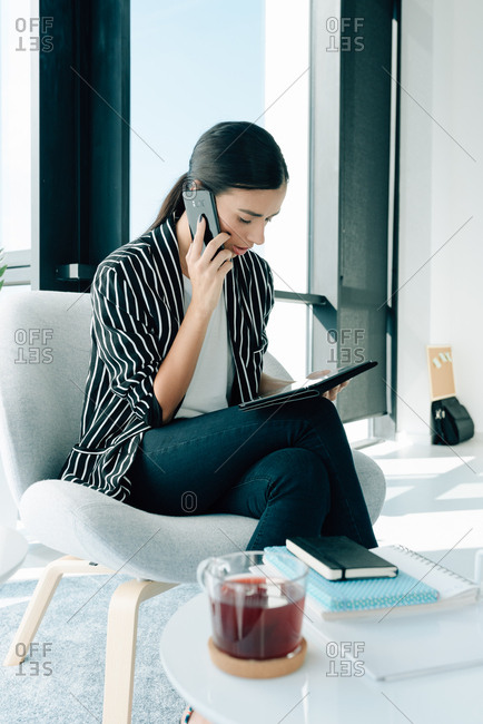 Young business woman looking at her tablet and speaking on her phone