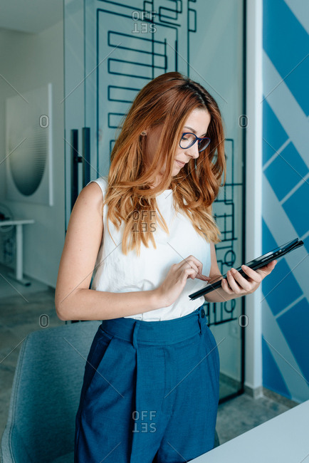 Young redhead business woman holding a meeting in modern office while looking at her tablet