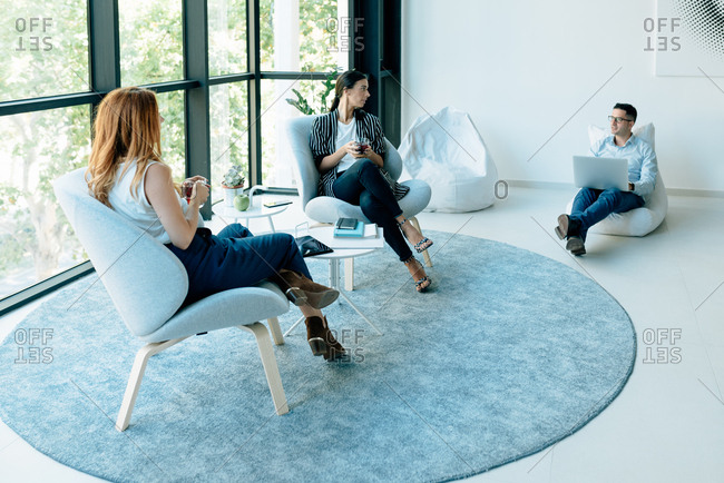 Three colleagues having a conversation in casual atmosphere in modern office