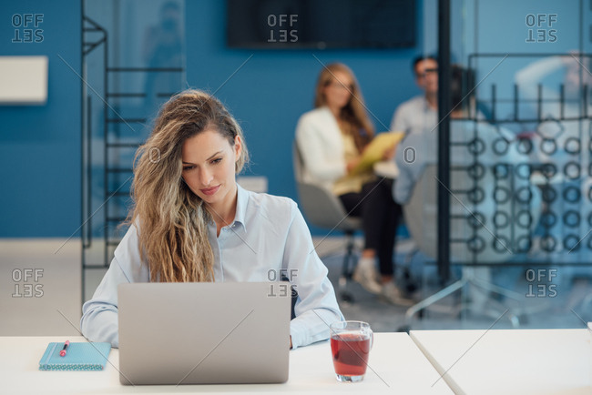 Woman working on her laptop while colleagues have a meeting in background