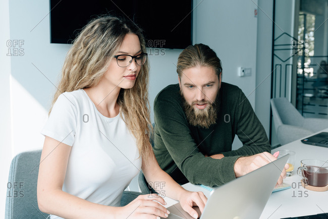 Young man with beard working on computer with his female colleague