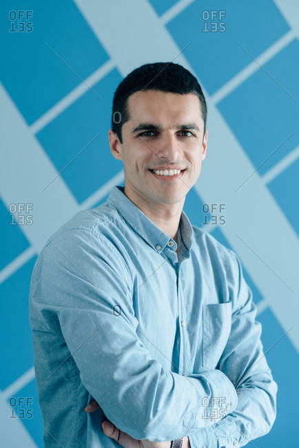 Portrait of young man in a blue shirt crossing his arms