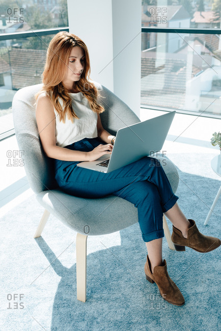 Young business red hair woman working on her laptop in modern office