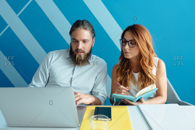 Man and a woman colleagues sitting next to each other and working on a laptop