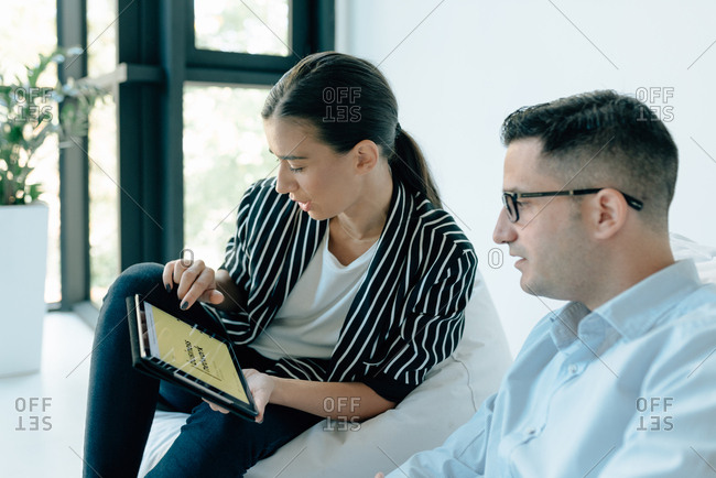 Two colleagues sitting on beanbag chairs while looking at tablet