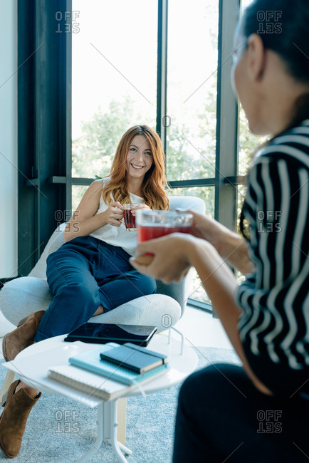Two young business women sitting on a break talking to each other and drinking tea in modern office