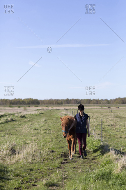 Full length of woman with horse walking on grassy field against sky during sunny day
