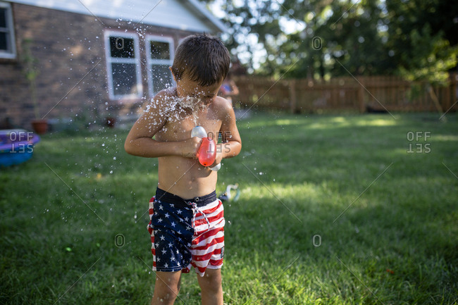 Shirtless boy playing with water bombs while standing on grassy field at backyard
