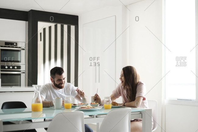 Happy young couple having breakfast at dining table in rental house