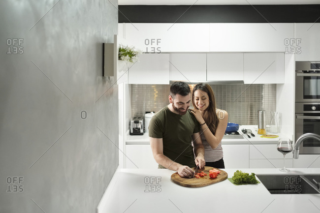 Smiling boyfriend chopping tomatoes in kitchen by loving girlfriend at rental house