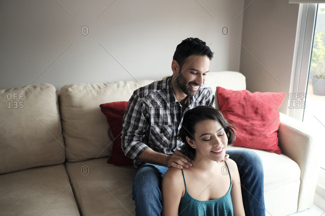 Smiling boyfriend massaging girlfriend's neck while sitting on sofa at home