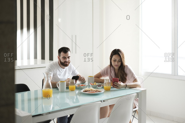 Young couple using mobile phones while having breakfast at dining table in rental house