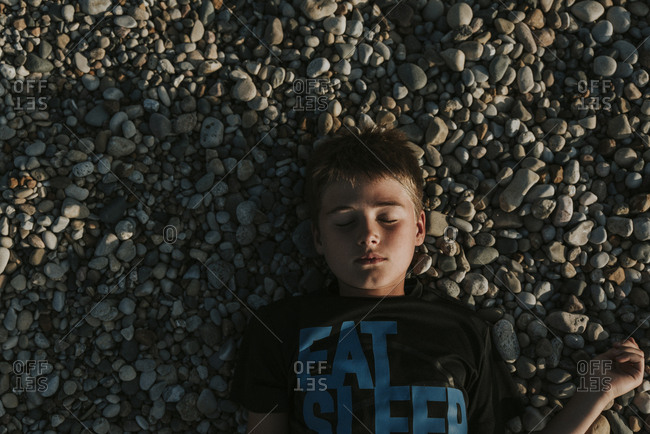 Overhead view of boy with eyes closed lying on pebbles at beach during sunset