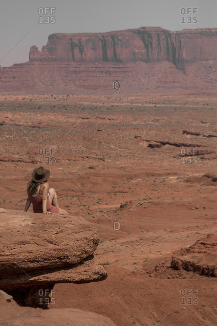 Rear view of female hiker looking at buttes while sitting on rocks against sky in Monument Valley Tribal Park during sunny day