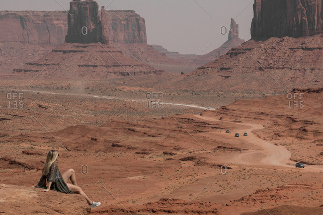 Side view of female hiker looking at buttes while sitting on rocks in Monument Valley Tribal Park during sunny day