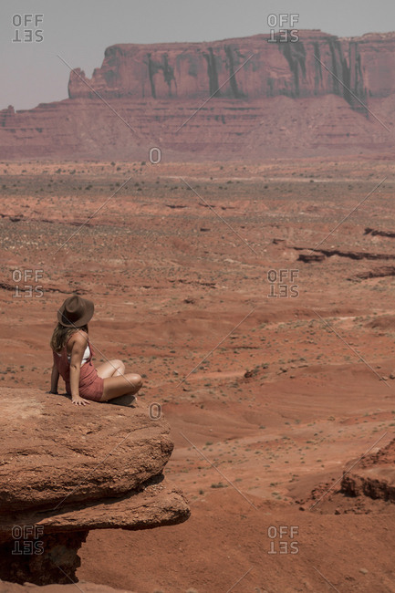 Female hiker looking at buttes while sitting on rocks against sky in Monument Valley Tribal Park during sunny day