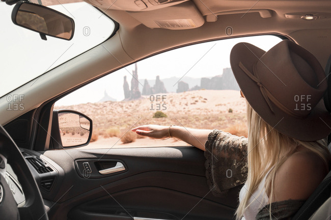 Side view of woman wearing hat while traveling in car at Monument Valley Tribal Park